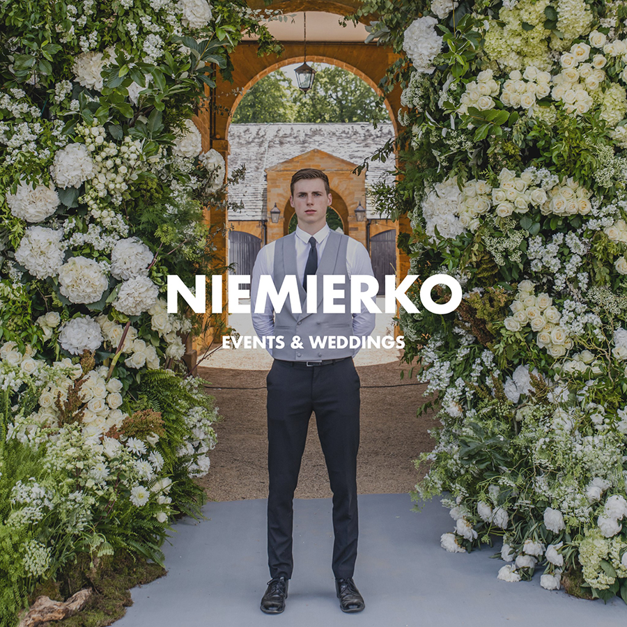 Brand image for Niemierko, one of Mark's hosts stands before an archway surrounded by white florals with tons of greenery