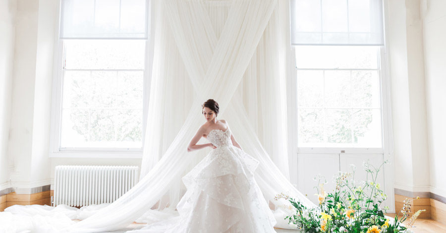 A model in a wedding gown stands before a white wall draped with sheer fabric in a cross between two windows. Credit Amanda Karen Photography