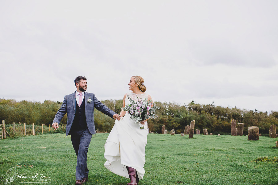 Bride and groom walking across a field. She holds a huge bunch of flowers, they're laughing and chatting as they walk. By Hannah Timm Photography at Coed Hills