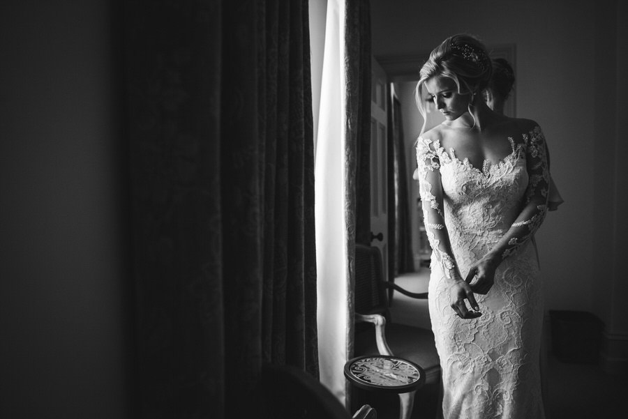 Emma puts the final touches to her wedding dress by Simon Biffen Photography