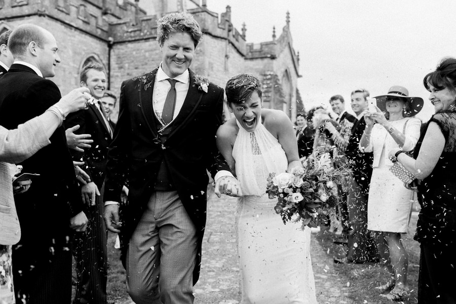Rosie and Tom walk the confetti line after getting married by Simon Biffen Photography