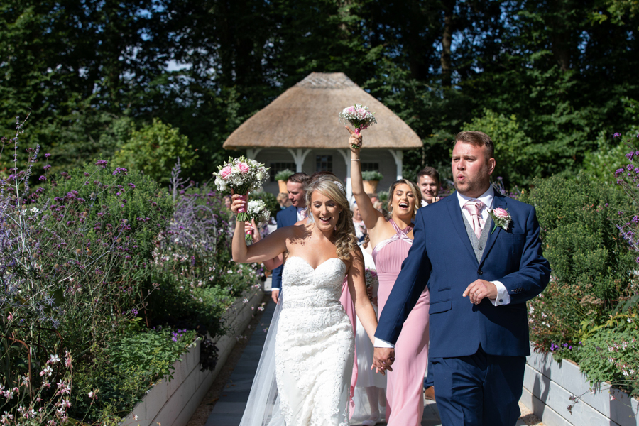 Danielle and Jason dancing down the aisle at Deer Park Hotel Devon by Evolve
