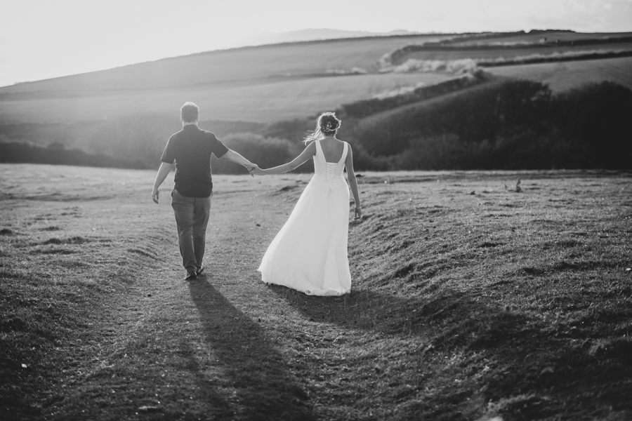 Nikita and Sam walking the clifftops at The Cow Shed Weddings in Cornwall by Evolve