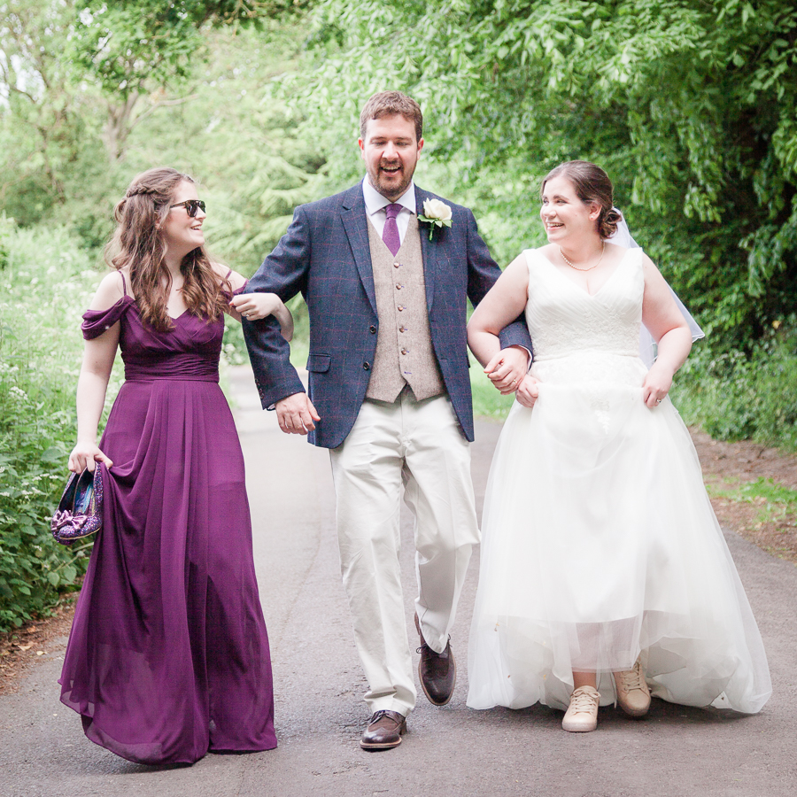Bridesmaid Becca walks arm-in-arm with Stewart and Jen to their wedding reception - Dom Brenton Photography