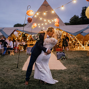 Couple celebrating their wedding in front of a tipi with festoon lights