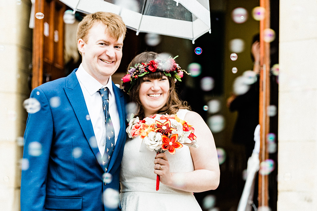 Newlyweds grinning as guests blow bubbles instead of confetti, Queen Bea Photography