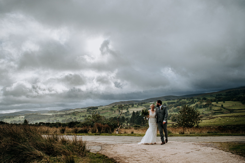 Bride and groom in a wide open rural space with moody cloudy sky and hillsides behind them