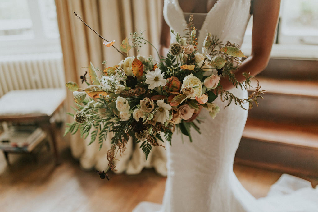 Horizontal wedding bouquet in autumnal colours with Japanese anemone, ferns and seedheads