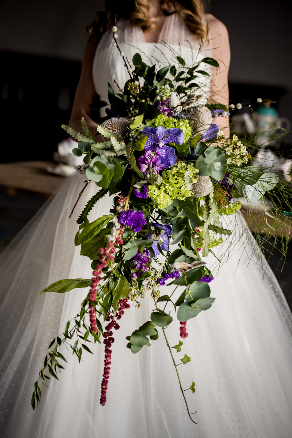 Bride holding trailing bouquet in green, purple with ivy and grasses