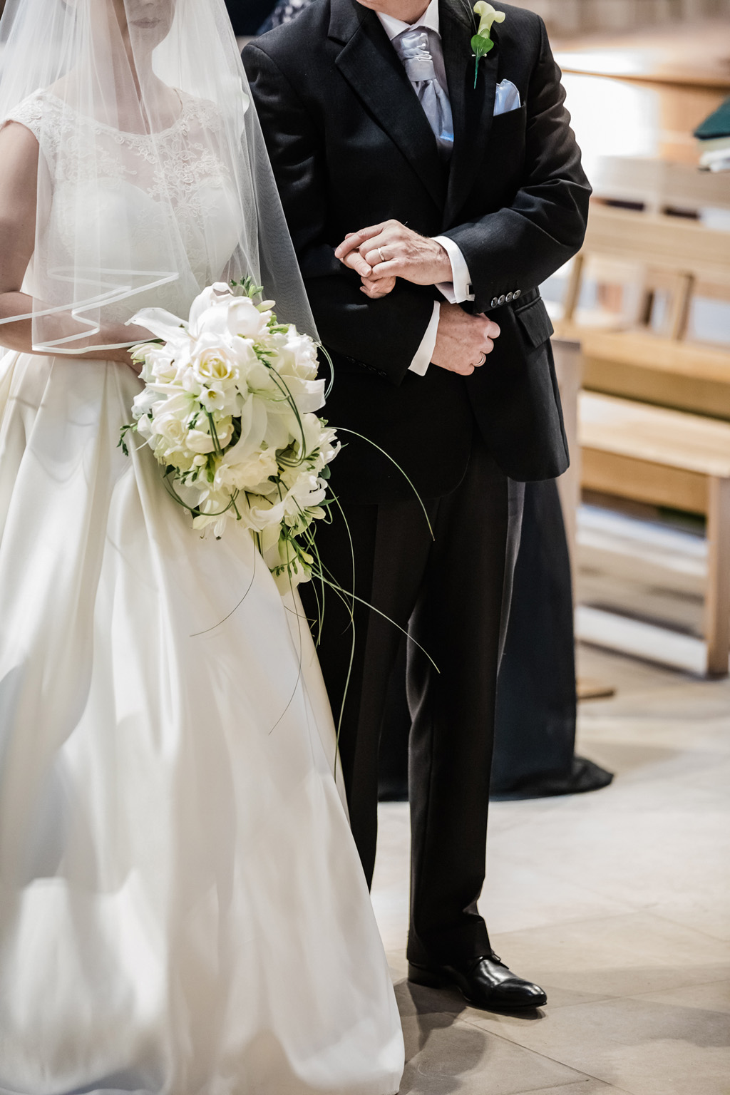 Formal wedding with bride and groom, bride holds a structured trailing bouquet in white with grasses