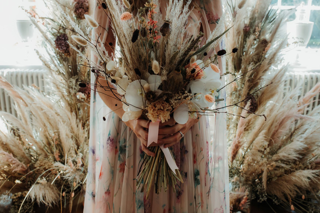 Bride in a colourful dress holds a boho bouquet with grasses and seedheads, the background is pampas grass