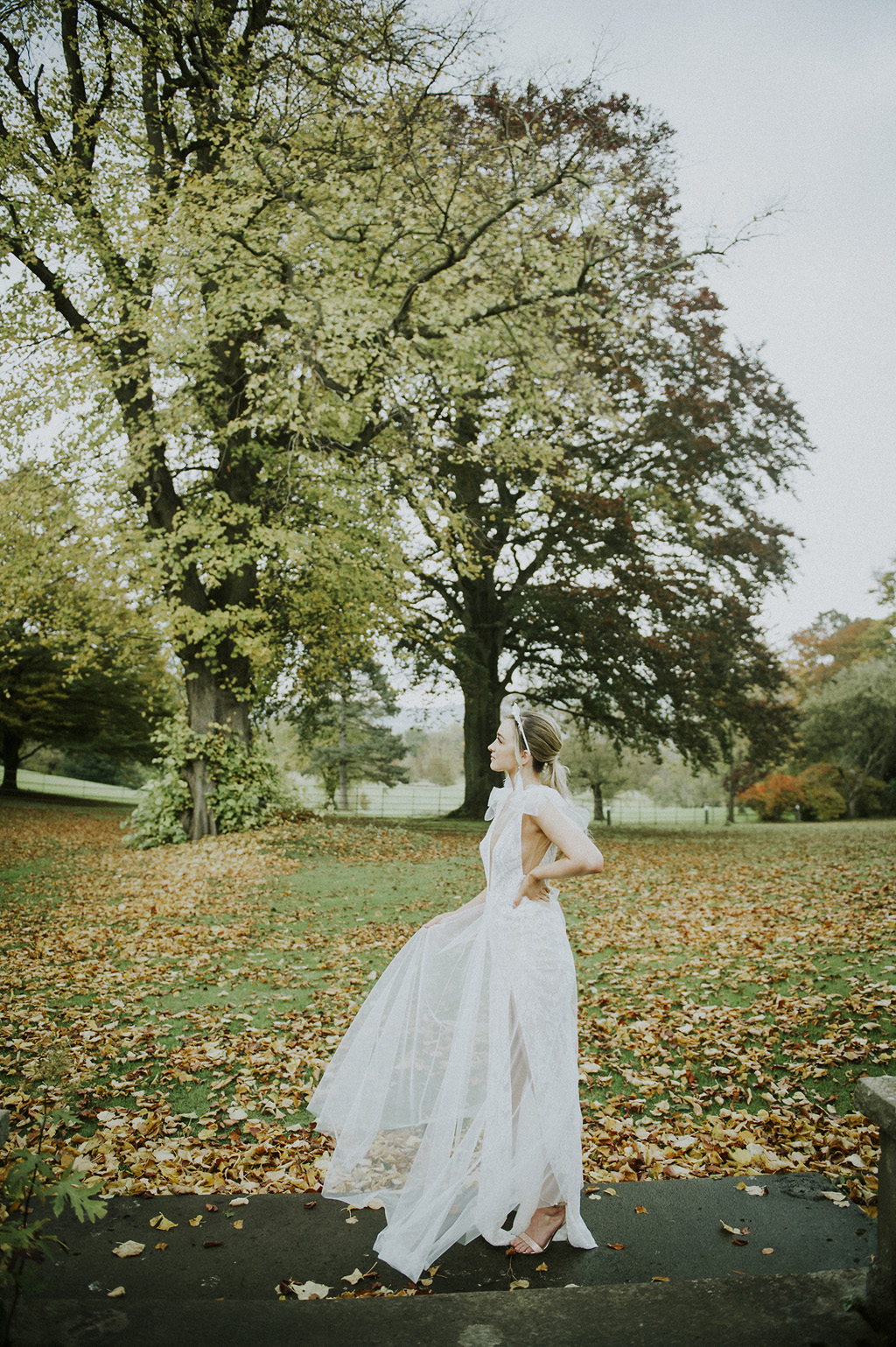 A girl in a modern wedding dress stands in a  park. There are autumn leaves on the grass, and mature trees in the background.