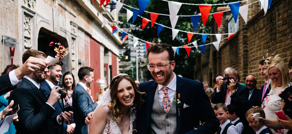 Bride and groom laugh as guests throw confetti. There's red white and blue bunting above
