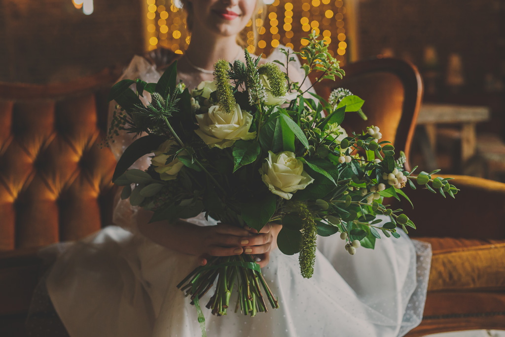 green bouquet held by a bride - includes ivory roses and lots of leaves, with eucalyptus and spring blooms. Photographer credit Neil Senior - Norfolk