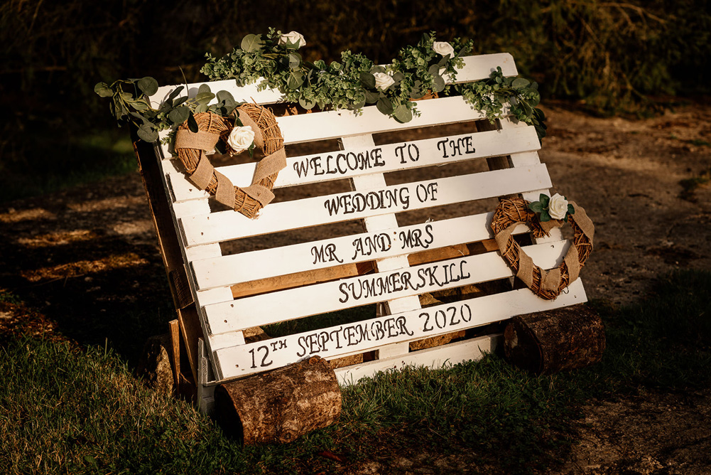 Wedding sign on a painted white palette, decorated with willow hearts and foliage
