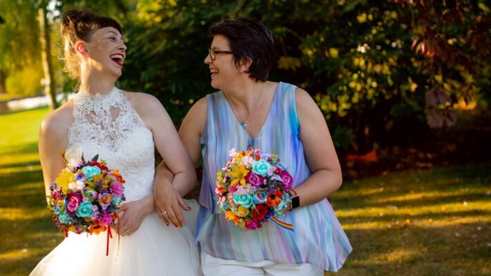 Two brides on their wedding day. The bride on the left wears a white sleeveless dress with a high neck and lace detailing. The bride on the right wears a pastel rainbow sleeveless top in a light fabric, with white trousers. Both hold rainbow coloured posy bouquets and they're beautiful. By Artisan X Photography