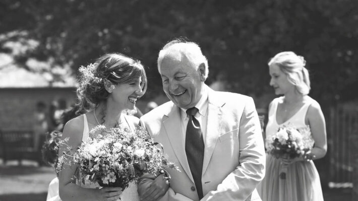 A bride with her dad on her wedding day. They're arm in arm, talking and smiling naturally together. She holds a bouquet of flowers and a bridesmaid walks in the background. Photography credit Lasting Impressions by Lucy