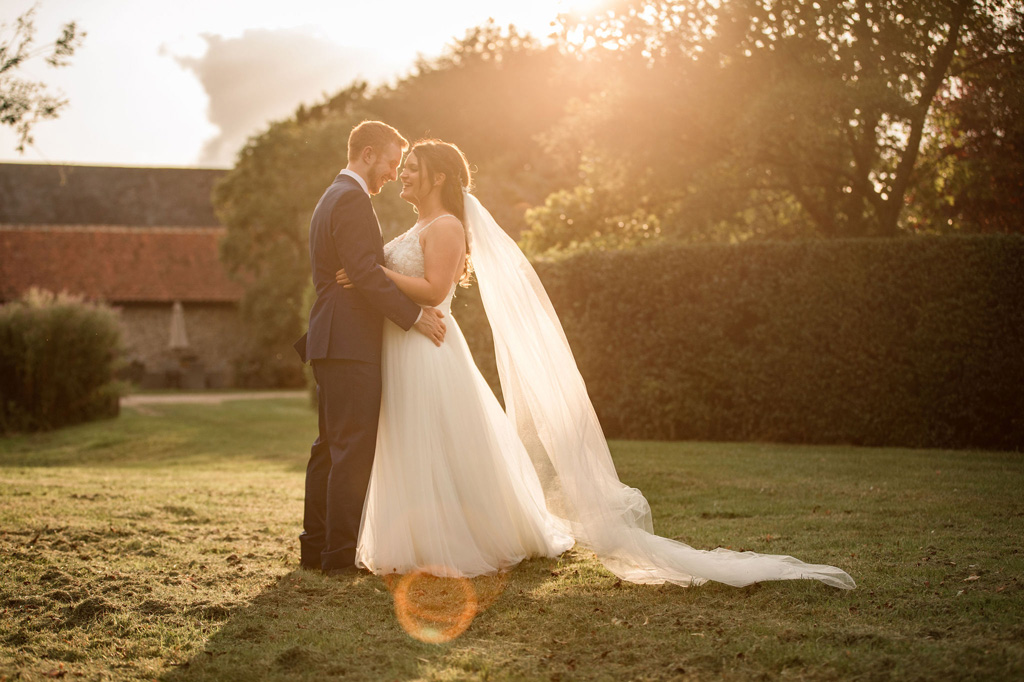 A bride and groom pose for a portrait at golden hour. She's wearing a full length veil which is beautifully lit by the sun. Credit Becky Harley Photography