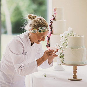 Emma at Scrumptious Bakes by Emma is adding detail to a 2 tier wedding cake. She's wearing a hair band and a white coat