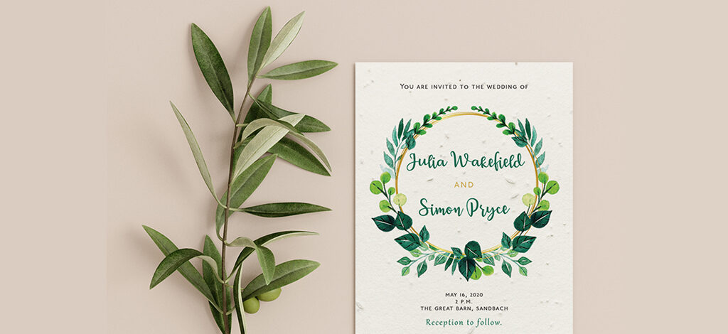 Example of a wedding invitation by Little Green Wedding, placed alongside a sprig of eucalytpus. The invitation has green floral wreath with the couples names in the centre and text above and below