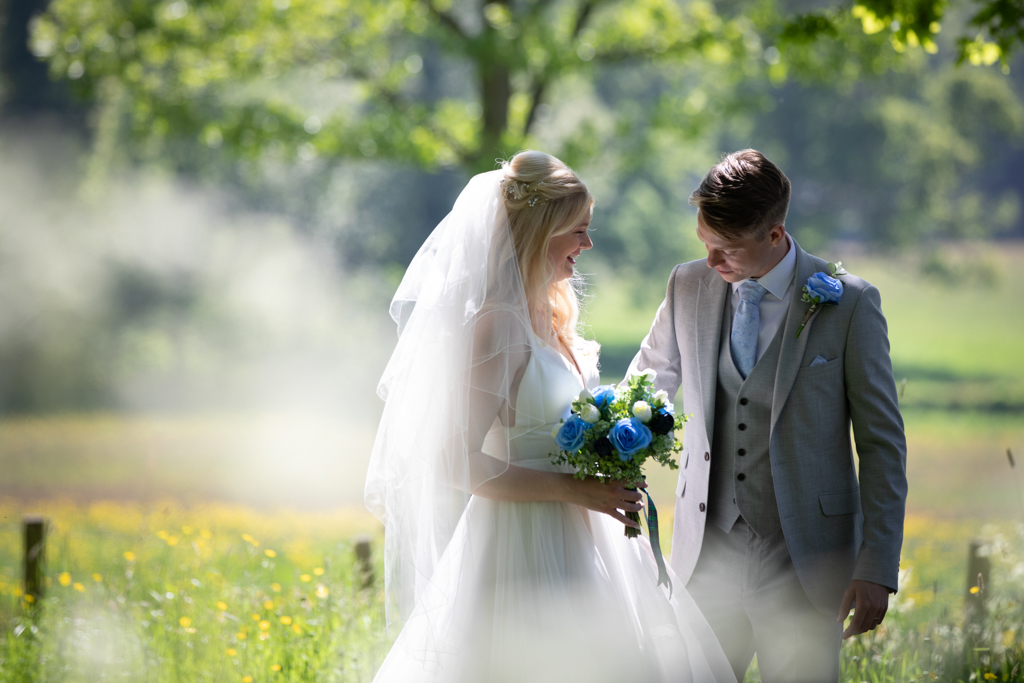 A bride and groom in dappled shade with a field of buttercups behind. She's holding a blue and white bouquet, and her veil catches the sunlight. He's wearing a pale grey suit and waistcoat with blue tie and buttonhole. By Devon wedding photography by Evolve