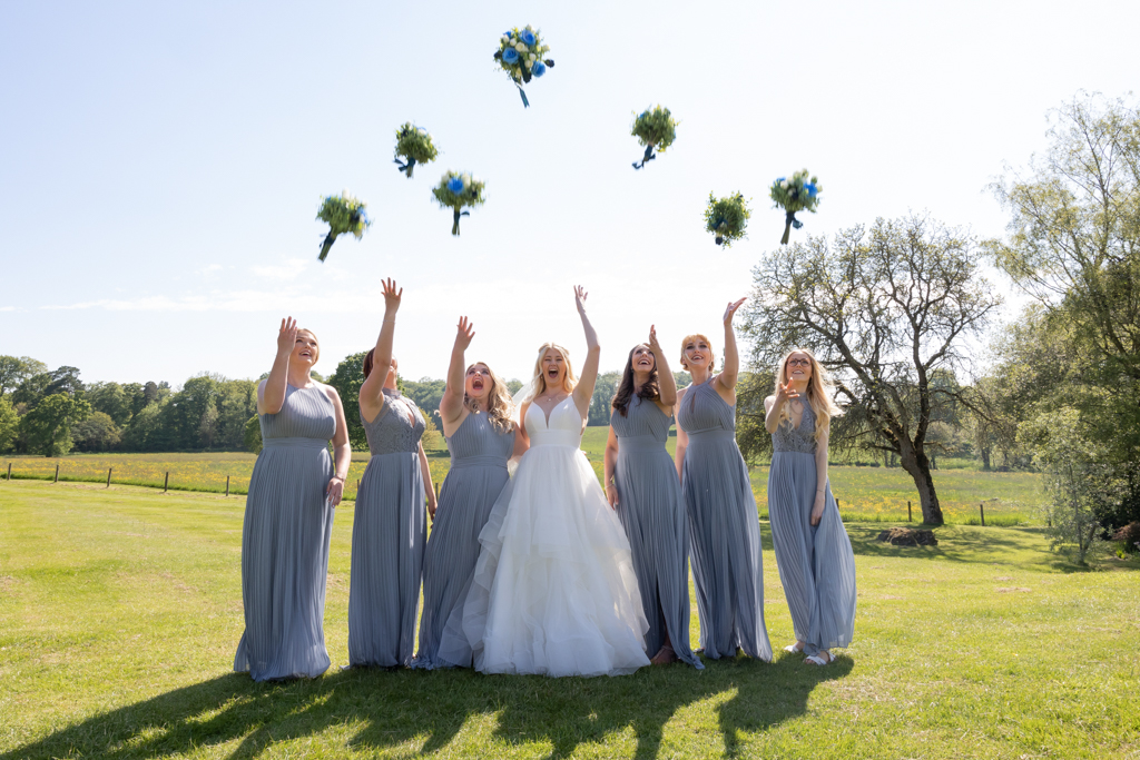 A bride and her six bridesmaids throw their bouquets in the air. The bridesmaids are in pale blue grey dresses. By Evolve wedding photographers in Devon