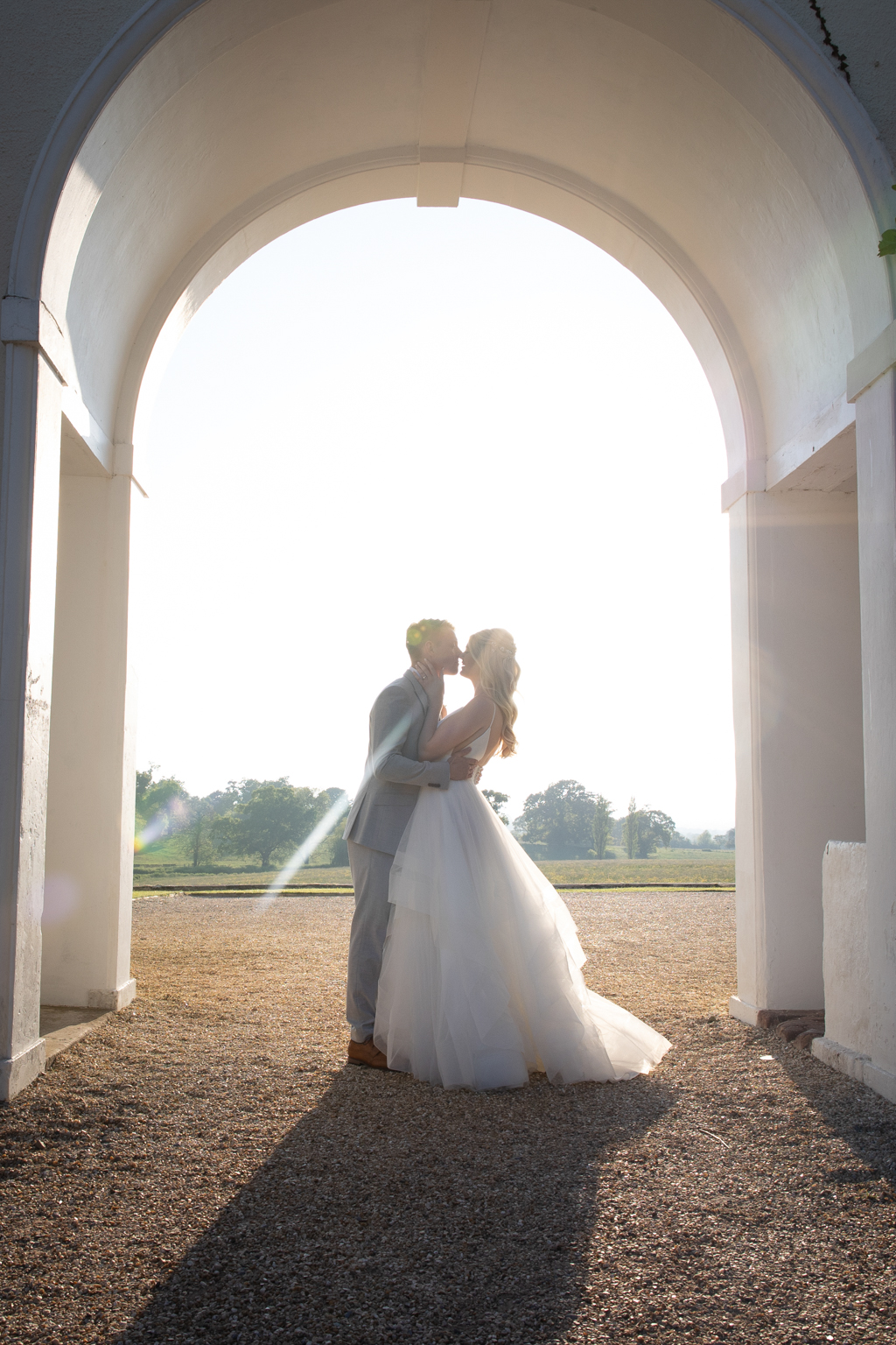 A beautiful image of a bride and groom below an archway at Rockbeare Manor. The sunlight behind them lights her dress, and they're about to kiss. By Evolve Photography Devon