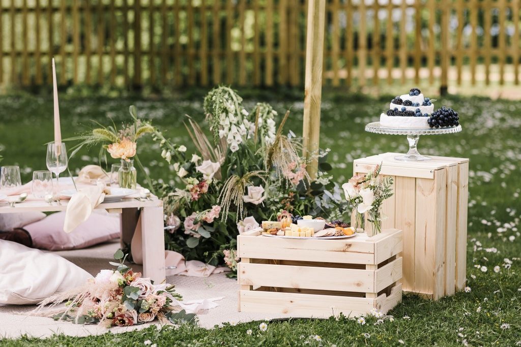 A wedding picnic setup with wooden crates, soft pink cushions and low wooden tables surrounded by pink florals and foliage, set out on a field of daisies. Styled by Lucy Bull Weddings and photographed by Danielle Smith Photography