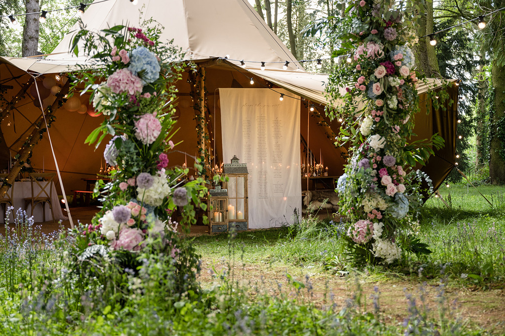 a wedding teepee entrance with hydrangea floral displays with blues, pinks and lots of foliage, festoon lighting and bluebells on the ground