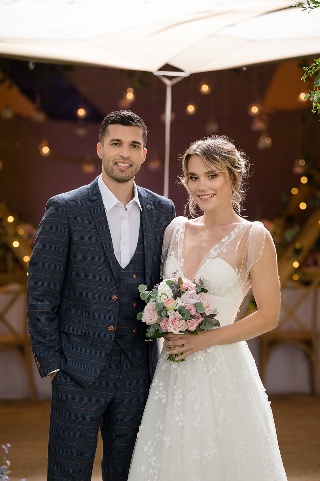 model bride and groom stood smiling towards the camera. She holds a country style bouquet and wears a white patterned dress. He's in a smart navy suit with no tie and an open collar