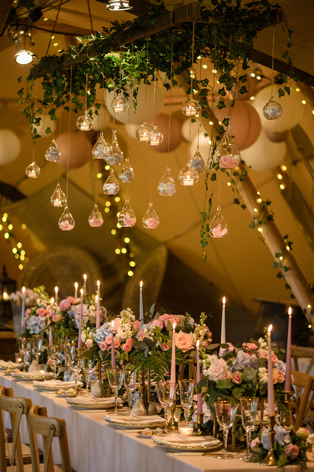 opulent table styling with candles and twinkly lights, blue and pink florals inside a teepee for a boho wedding
