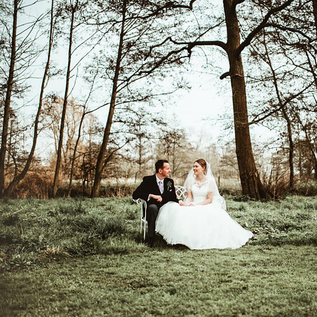 Easton Grange wedding - a couple sit in an open woodland, she's wearing a beautiful white dress and they're smiling at each other. By Beth Beresford Photography