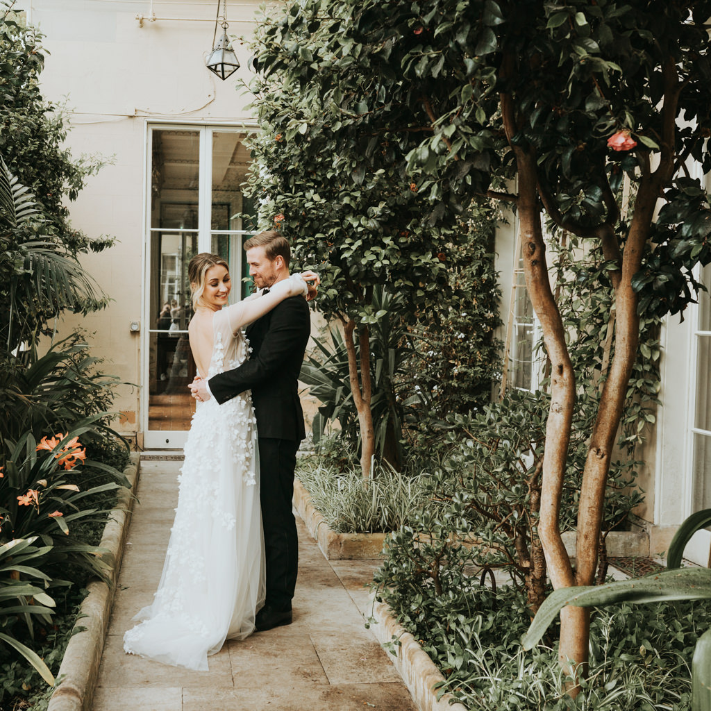 Newlyweds stand with their arms around each other, on a stone path in a courtyard by beautiful olive trees. Beth Beresford Photography