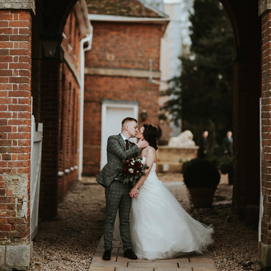 A bride and groom kiss outside the wedding venue. Captured by Beth Beresford Photography at Hintlesham Hall