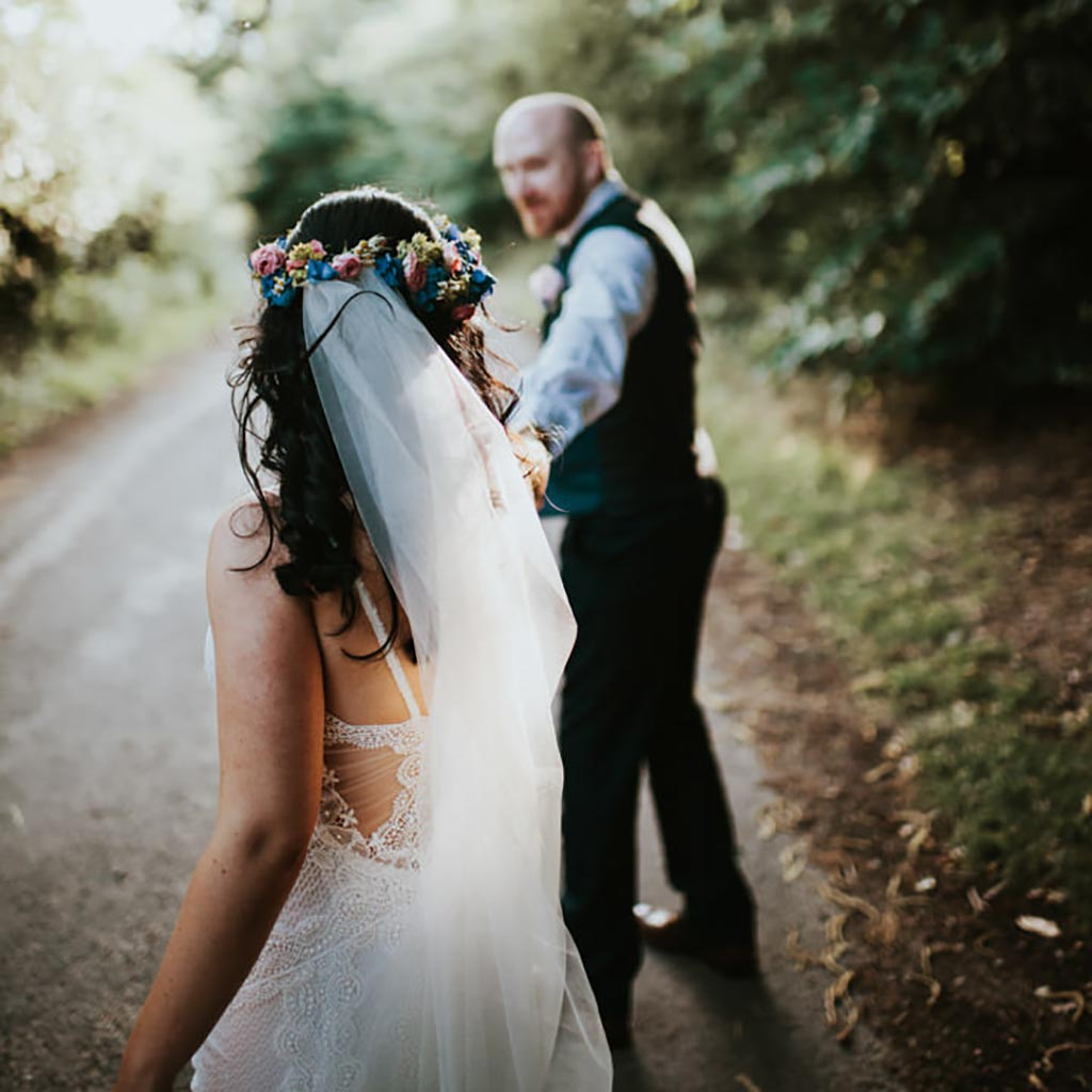 A couple walk along a country road, the sun lights her boho veil and he turns to look back at her. Captured by Beth Beresford Photography