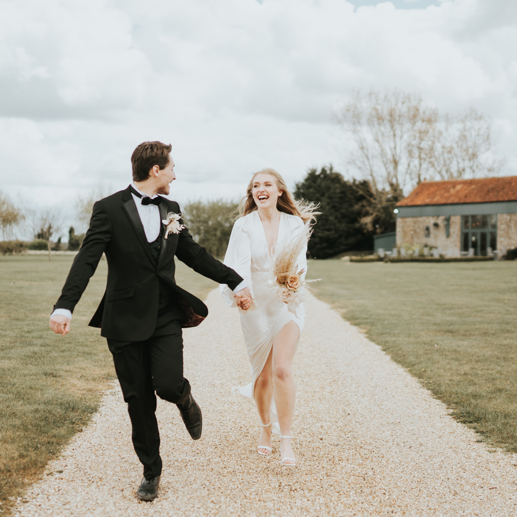 A modern bride and groom run along a path towards the camera, laughing. Captured by Beth Beresford Photography at Pentney Abbey in Norfolk