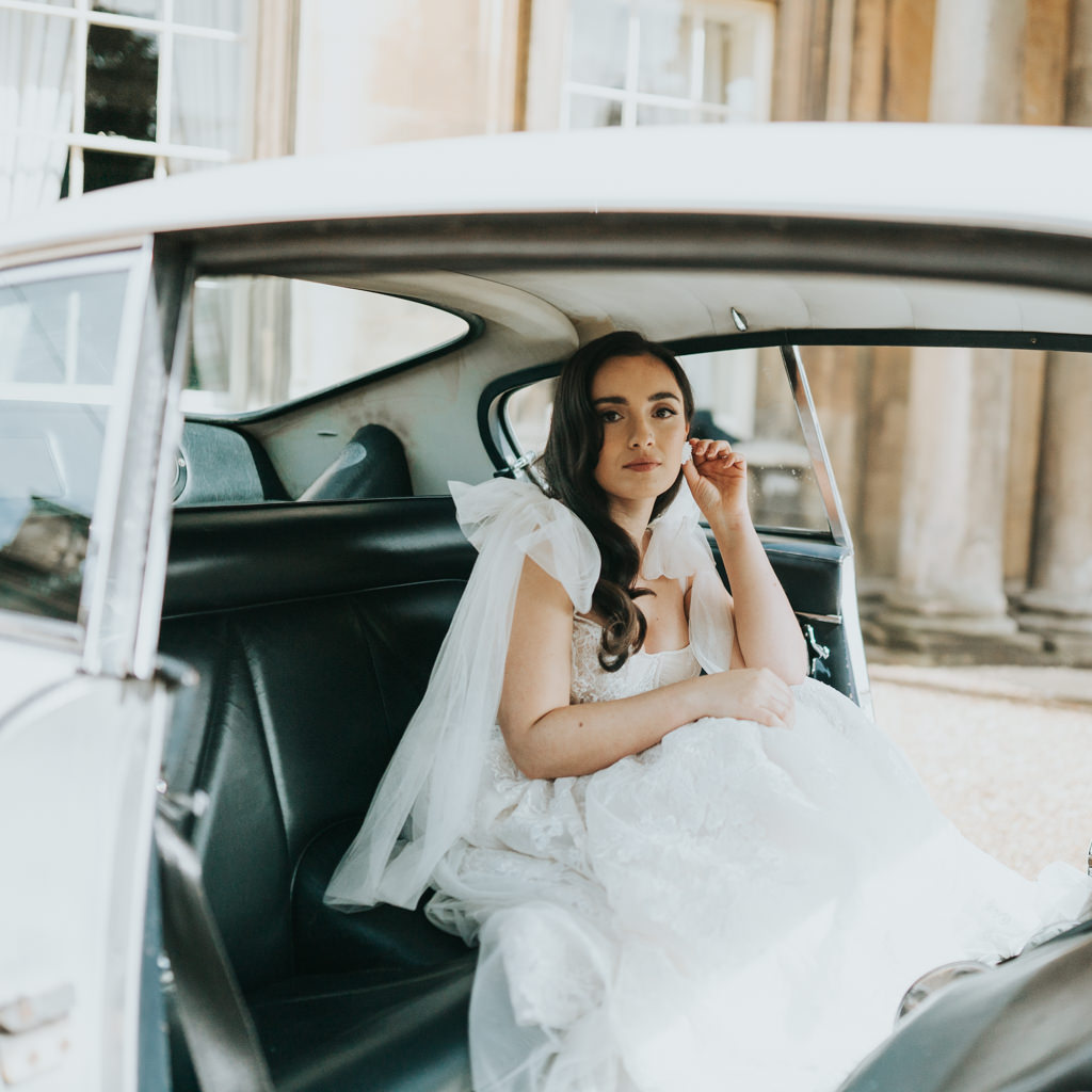 A bride sits in the back of a wedding car, wearing a modern wedding dress and looking thoughtfully towards the camera. Captured by Beth Beresford Photography at The Prestwold Hall in Loughborough