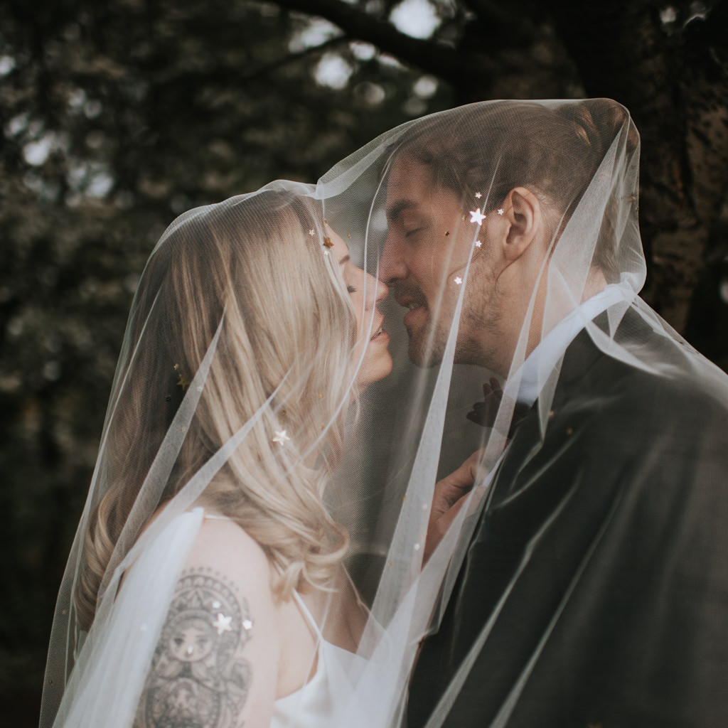 Newlyweds share a kiss under her wedding veil. The bride is blond with a tattoo on her shoulder. Captured by Beth Beresford Photography