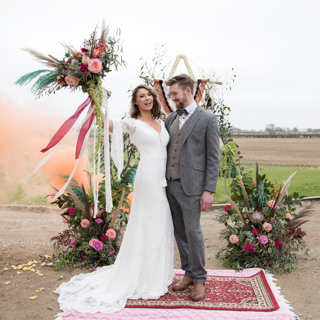 A boho bride and groom stand on a rug outside their venue. She lifts a bouquet with pampas grass and pink ribbons. There are flower arrangements behind them. Yorkshire wedding photography by Daze Photography