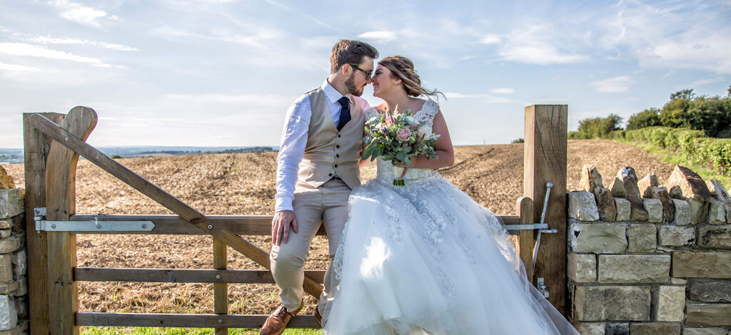 A bride and groom sit on a gate in the Yorkshire countryside - image by Daze Photography