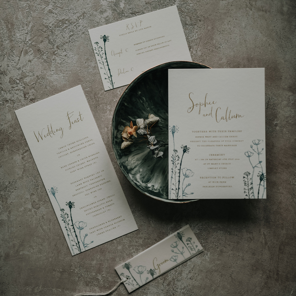 Delicate wedding invitations arranged on a bowl with dried flowers. There's a menu, invitation, RSVP and place card with vellum overlay. They have an artisan look with floral illustrations. By Inkflower Press