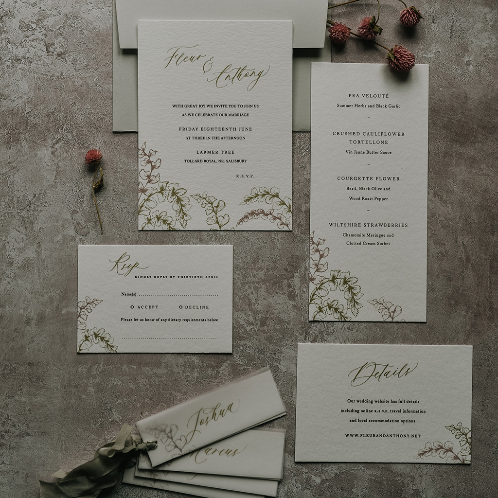 Elegant wedding stationery set with foliage illustration of ornamental ferns. There's an invitation, menu, RSVP, details card and place cards with ribbon. By Inkflower Press