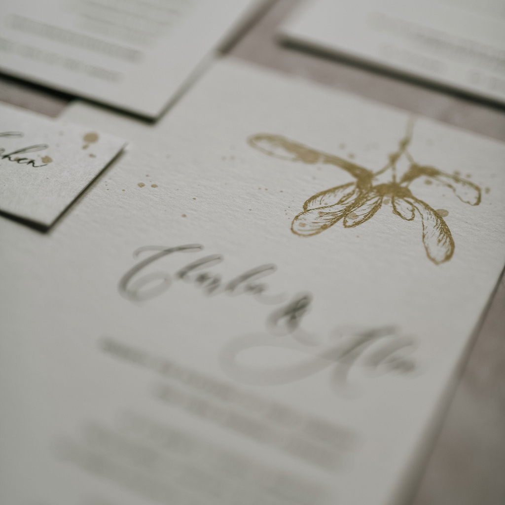Wedding invitation close up of a maple seed illustration, beautifully done with artisan style ink splatters. By Inkflower Press