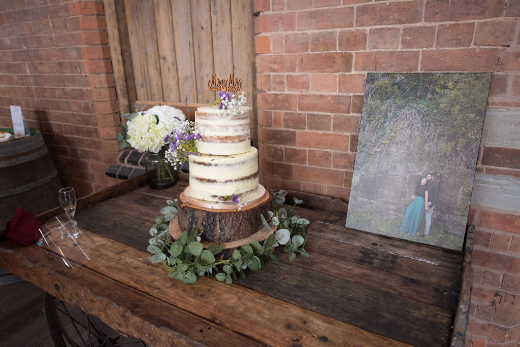 A 2 tier wedding cake with smooth buttercream in a rustic elegant style sits on a wooden table surrounded by eucalyptus leaves. There's a photo of a couple on the table, and a small bouquet of cream flowers in the background. Image by Bal Sandhu Photography