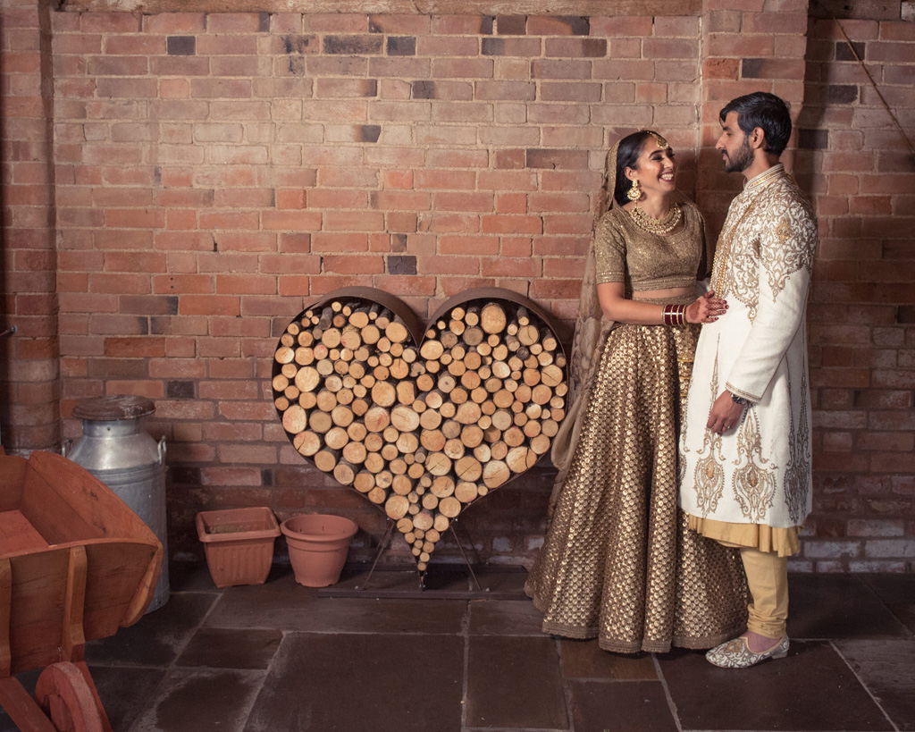 A bride and groom in Indian dress stand beside a heart decoration filled with log slices