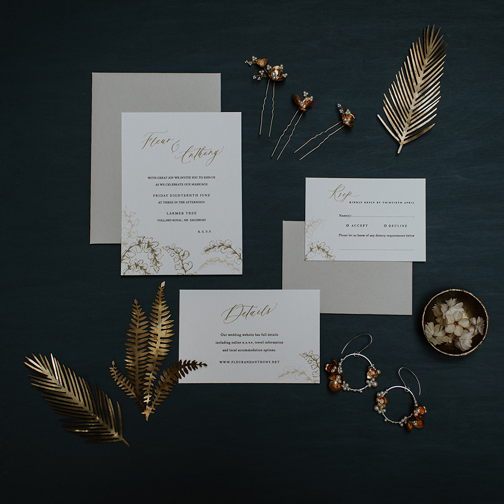 Arrangement of wedding stationery with bridal jewellery and gold leaves. There's an invitation, RSVP and details card, all with fern illustrations. By Inkflower Press