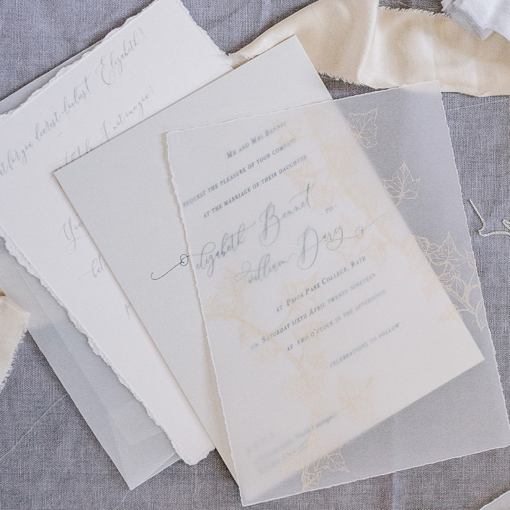 Wedding invitation suite with a vellum overlay printed with gold ivy leaves. There's a handwritten letter in modern calligraphy behind the main invitation, and a sheer vellum envelope. By Inkflower Press