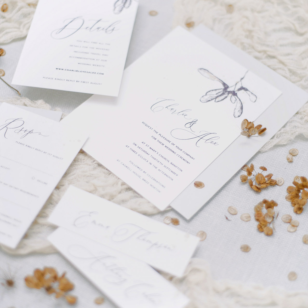 Autumnal looking wedding stationery set with botanical illustration - a maple seed is printed in soft grey black. There's an invitation, details card, RSVP and place cards. By Inkflower Press