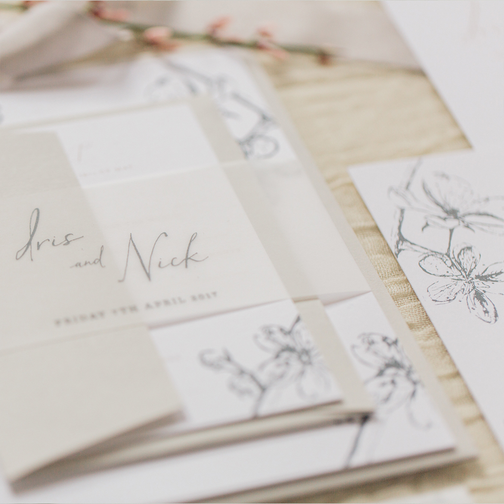 Layered wedding invitation set with a vellum belly band. Envelopes are in a soft ecru and the invitations have a fine art style cherry blossom print with a calligraphy font. By Inkflower Press