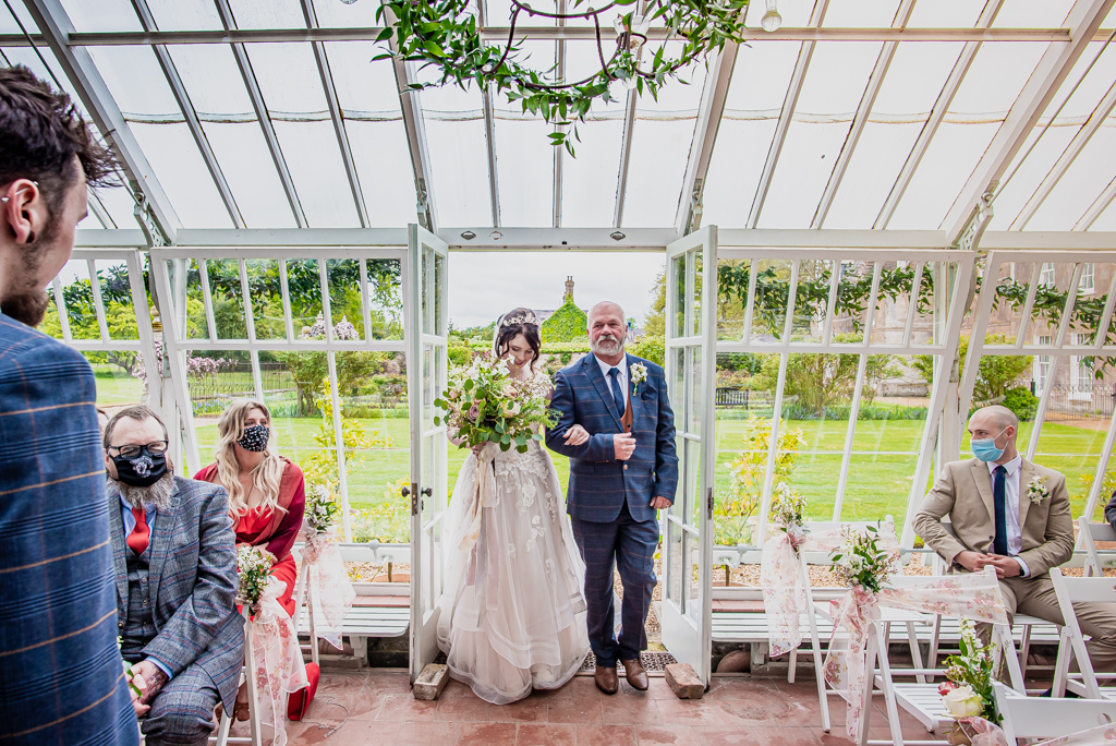 Photo of Lorna and Keanu's wedding at Stradsett Hall. The venue is quirky with lots of foliage and greenery. There are 30 guests and the couple are in a blush wedding dress and blue check suit. Photography by Damien Vickers.